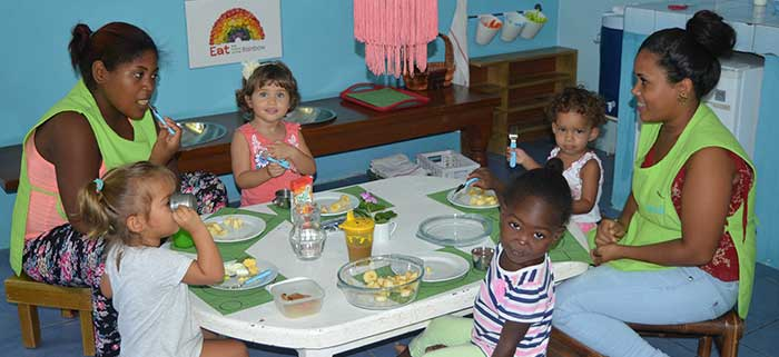 Children and staff share a meal