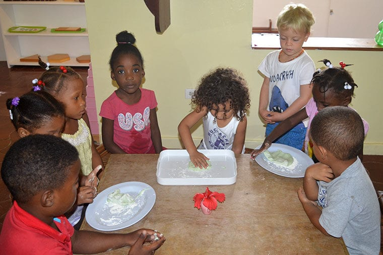 Children with dough around a table