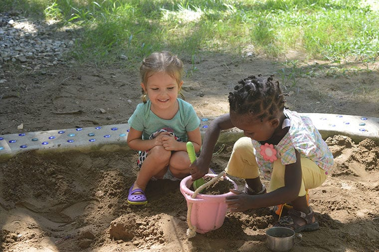 2 girls play in sandbox